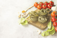 Raw pasta of tagliatelle with spinach and ingredients for cookin. G cherry tomatoes, spices, garlic, spinach leaves on a light background. Copy space. Food Stock Photography