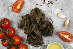 Raw pasta of tagliatelle with spinach and ingredients for cookin. G cherry tomatoes, spices, garlic on gray background. Top view. Food background Royalty Free Stock Photo
