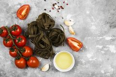 Raw pasta of tagliatelle with spinach and ingredients for cookin. G cherry tomatoes, spices, garlic on gray background. Top view, copy space. Food background Stock Image