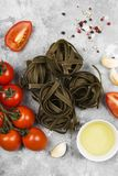 Raw pasta of tagliatelle with spinach and ingredients for cookin. G cherry tomatoes, spices, garlic on gray background Stock Image