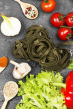 Raw pasta of tagliatelle with spinach. And ingredients for cooking cherry tomatoes, spices, garlic, spinach leaves, pepper, lettuce on a dark background. Top Stock Image