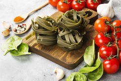 Raw pasta of tagliatelle with spinach and ingredients for cooking cherry tomatoes, spices, garlic, spinach leaves. On a light background Royalty Free Stock Image
