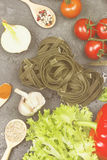 Raw pasta of tagliatelle with spinach and ingredients for cookin. G cherry tomatoes, spices, garlic, spinach leaves, pepper, lettuce on a dark background. Top Stock Photography