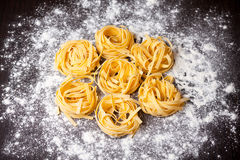 Raw pasta tagliatelle on table Royalty Free Stock Images