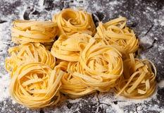 Raw pasta tagliatelle on table. Raw pasta tagliatelle with flour on table Royalty Free Stock Photo