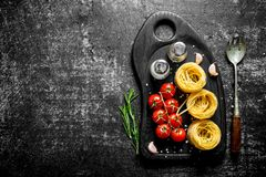 Raw pasta tagliatelle with tomatoes and spices on a cutting Board. On rustic background royalty free stock photos