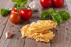 Raw pasta. With tomato, garlic and basil, selective focus Royalty Free Stock Image