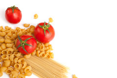 Raw pasta and tomatoes Stock Images