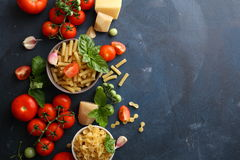 Raw pasta and tomatoes, food background. Raw pasta and tomatoes, dark food background Royalty Free Stock Images