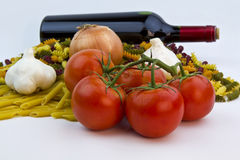 Raw pasta, tomatoes, garlic and red wine bottle. The main players of Team Pasta shot under soft lights Royalty Free Stock Images