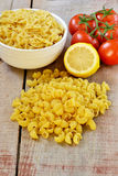 Raw pasta with tomatoes and lemon. On wooden background Stock Photography