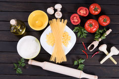 Raw pasta, tomatoes,mushrooms, flour and egg on black wooden table background. Top view Stock Images