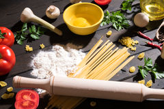 Raw pasta, tomatoes,mushrooms, flour and eggs on black wooden table background, top view. Royalty Free Stock Photos