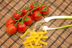Raw pasta, tomatoes and onions. On wooden background Stock Images