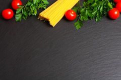 Raw pasta with tomatoes and parsley.  Royalty Free Stock Images