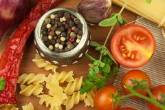 Raw pasta with tomatoes and parsley on a wooden background. Preparation diet food. The recipe for a simple dinner. Stock Photos