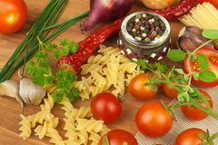 Raw pasta with tomatoes and parsley on a wooden background. Preparation diet food. The recipe for a simple dinner. Stock Photo