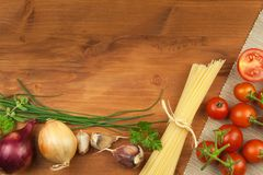 Raw pasta with tomatoes and parsley on a wooden background. Preparation diet food. The recipe for a simple dinner. Royalty Free Stock Photos