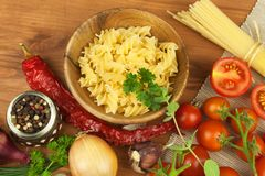 Raw pasta with tomatoes and parsley on a wooden background. Preparation diet food. The recipe for a simple dinner. Royalty Free Stock Photo