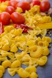 Raw pasta and tomatoes. Ingredients for cooking italian food Royalty Free Stock Images