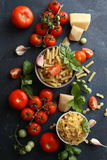 Raw pasta and tomatoes. On slate Stock Image