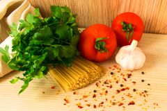 Raw pasta with tomatoes and spices and herbs on the table stock image