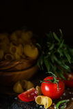 Raw pasta and tomatoes in wood bowl. Dark photo, copy space Royalty Free Stock Photo