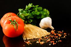 Raw pasta with vegetables and spices, ingredients for pasta royalty free stock images