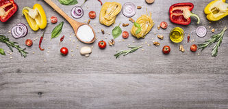 Free Raw Pasta With Peppers And Cherry Tomatoes With A Wooden Spoon And Salt On A Long Gray Wooden Background Top View Place For Text,f Royalty Free Stock Photo - 63393945