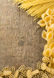 Raw pasta on wood background Stock Image