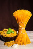 Raw pasta on wood background Stock Photography