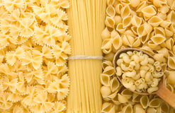 Raw pasta and wood spoon Royalty Free Stock Images
