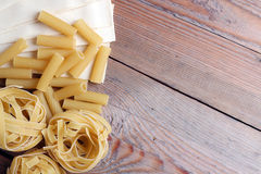 Raw pasta on a wooden background Royalty Free Stock Images