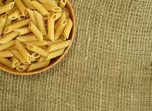 Raw pasta in wooden bowl on sacking Royalty Free Stock Images