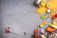 Raw pastas with tomato sauce on grey countertop. View from above, copy space. Royalty Free Stock Photo