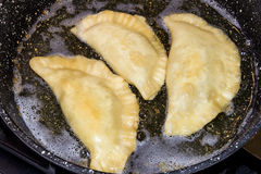 Raw pasties with meat fried in a pan in sunflower oil stock image
