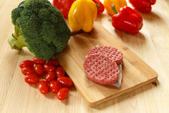 Raw patties of minced meat on a wooden board Royalty Free Stock Image