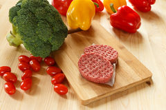 Raw patties of minced meat on a wooden board Royalty Free Stock Photography