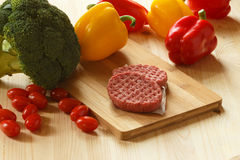 Raw patties of minced meat on a wooden board Stock Images