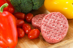 Raw patties of minced meat on a wooden board Royalty Free Stock Photos