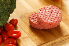 Raw patties of minced meat on a wooden board Royalty Free Stock Photo