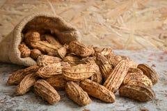 Raw peanut in hemp sack on wooden background Stock Photo