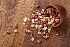 Raw peanuts mix in overturned ceramic bowl isolated over rustic wooden backround, top view, close-up. Shelled raw peanuts mix in overturned ceramic bowl Stock Photography