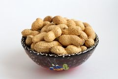 Raw peanuts in shell on clay cup on white background stock photography