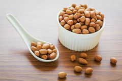 Raw peanuts on spoon and bowl Royalty Free Stock Photos