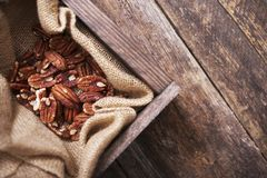 Raw Pecans in Wood Crate. Raw Pecans in Small Wood Crate and Canvas. Top View Royalty Free Stock Images