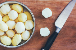 Raw peeled potatoes on old cutting board and kitchen knife close-up view from above Stock Images