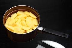 Raw peeled potatoes in pan stock image