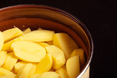Raw peeled potatoes in pot pan on black Stock Photography