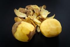 Raw peeled potatoes and potato peelings Stock Photography